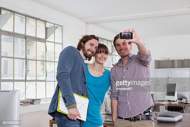 Three colleagues taking a selfie with smartphone in an office
