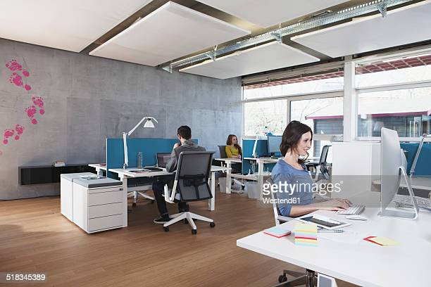 Three colleagues working in modern open space office