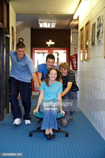 Three college boys pushing girl along on chair, smiling, portrait