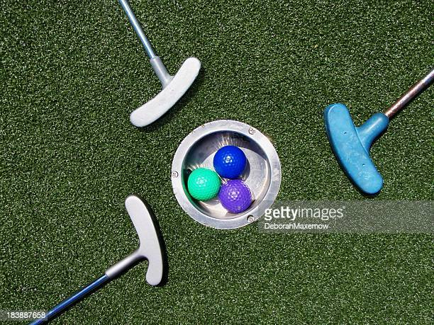 Three Colorful Golf Balls and Putting Irons Surround Astroturf Hole