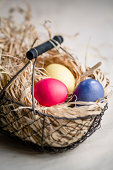 Three coloured easter eggs in basket filled with straw, close up
