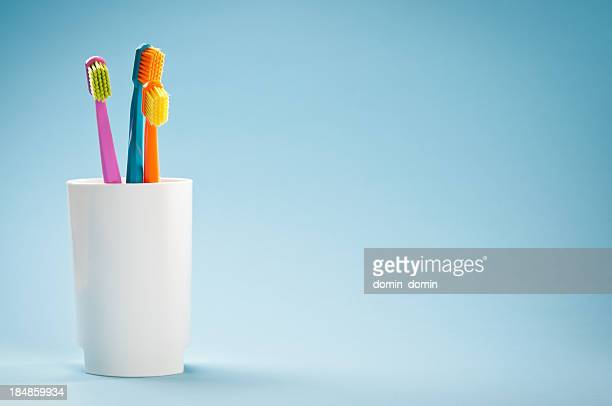 Three colourful soft toothbrushes in white mug on blue background