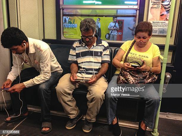 Three commuters comfortably Seated in the subway train Busy working on their electronic device Milano Italy