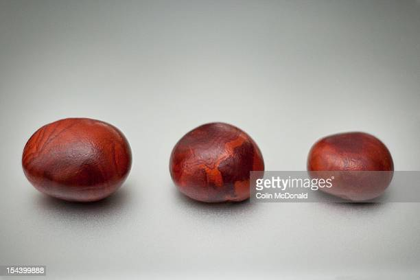 Three conkers on a silver background