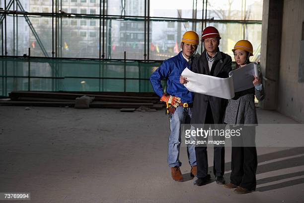 Three construction workers looking at blueprints, in empty unfinished room, portrait.