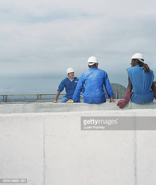 Three construction workers resting on building top