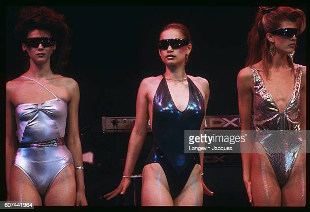 Three contestants wearing swimsuits and sunglasses walk on the stage of the first ever Miss Moscow beauty pageant