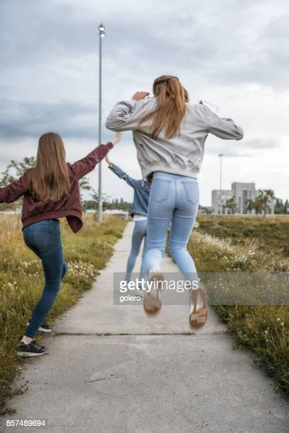 three cool teenage girls jumping up outdoors