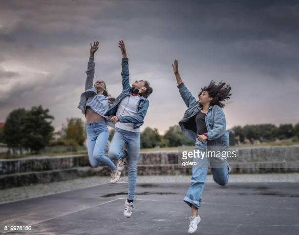 three cool teenage girls jumping up