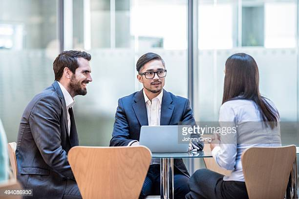 Three corporate business people in meeting with laptop.