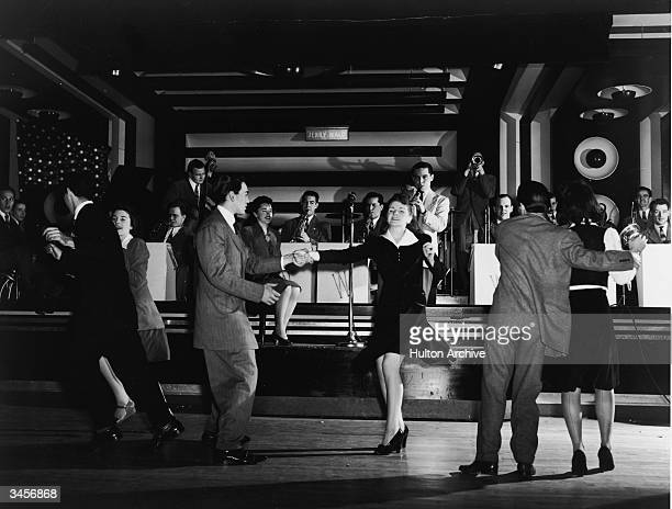 Three couple swing dance to the Jerry Wald Orchestra 1940s Vocalist Anita Boyer sits on the stage as the band plays