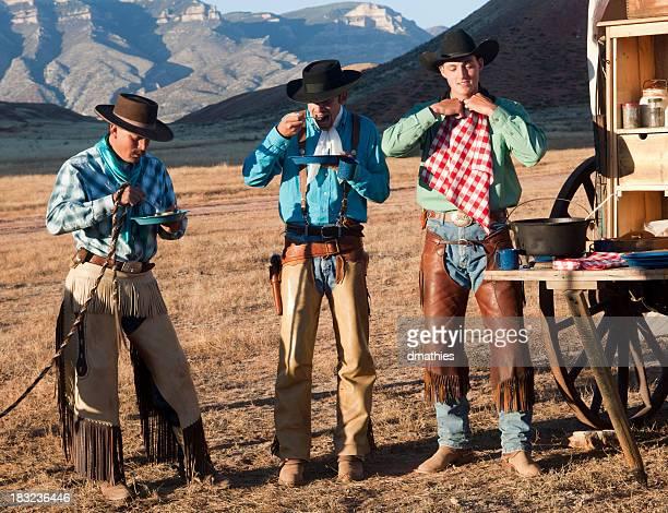 Three cowboys have meal at chuckwagon in Wyoming