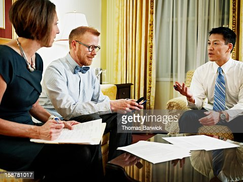 Three coworkers discussing project in hotel suite : Stock Photo