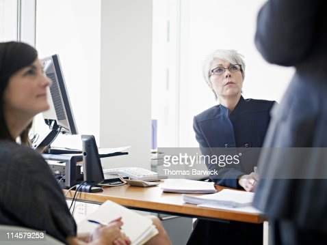 Three coworkers in discussion at desk in office : Stock Photo