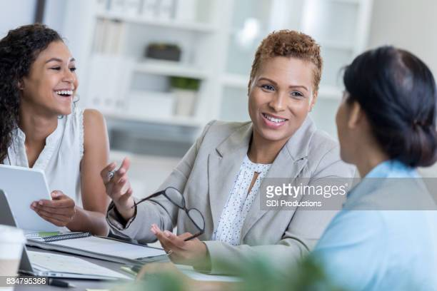 Three coworkers laugh together during meeting