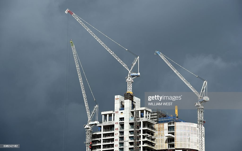 Three cranes work on top of a construction site in Sydney on June 1, 2016. Australia's economy defied market forecasts with stronger-than-predicted expansion in January-March, driven by net exports and household spending, strengthening expectations interest rates will remain on hold for some months. Economic growth expanded by 1.1 percent in the first quarter for an annual year-on-year reading of 3.1 percent, the highest in recent years and far above economists' estimates of 0.8 percent and 2.9 percent. / AFP / William WEST