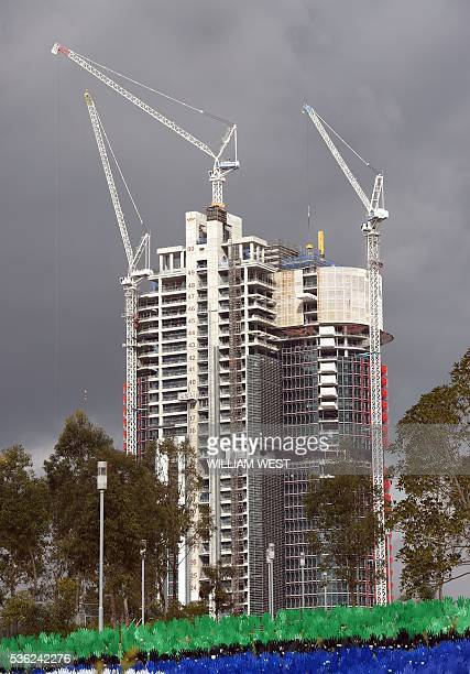 Three cranes work on top of a construction site in Sydney on June 1 2016 Australia's economy defied market forecasts with strongerthanpredicted...