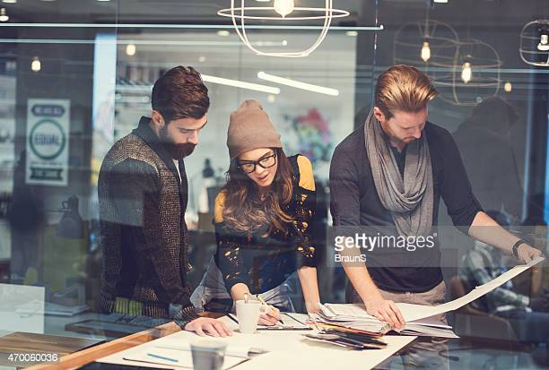 Three creative people working in the office.