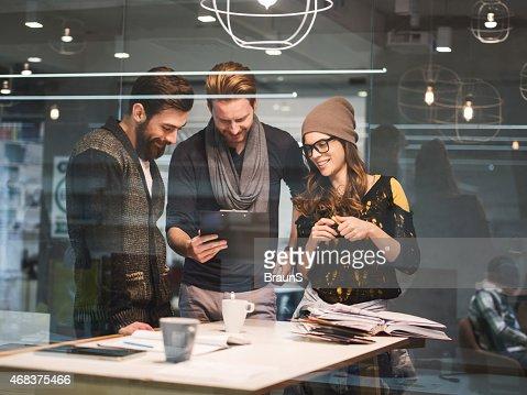 Tres de las personas creativas trabajan juntos en los trámites de la oficina.