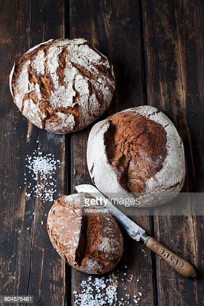 Three crusty breads, bread knife and scattered salt grains on dark wood