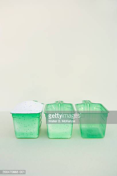 Three cups of powdered laundry detergent in varying amounts