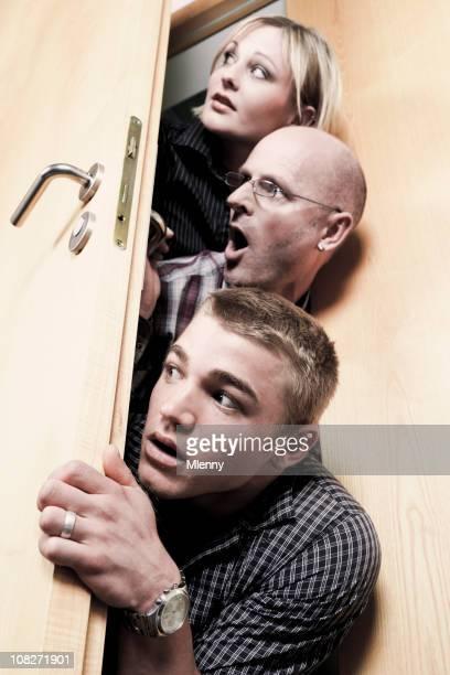 Three Curious People Peeking Around Door