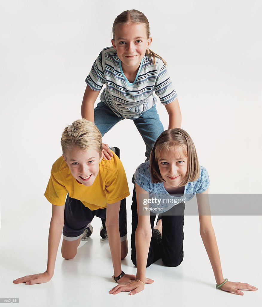 three cute blond preteen children are kneeling on each other making a human pyramid : Stock Photo