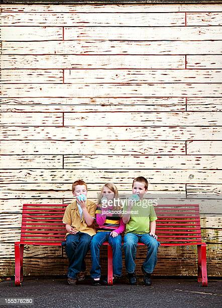 Drei Süße Kinder essen Zuckerwatte auf einer Bank