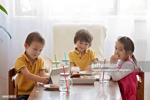 Three cute kids, eating breakfast at home