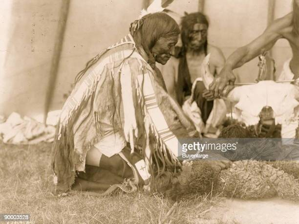 Three Dakota men seated or kneeling on ground one attending to bison skull