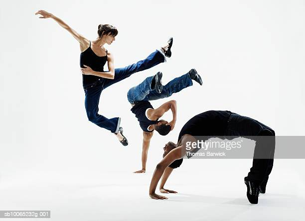 Three dancers in various poses on white background, side view