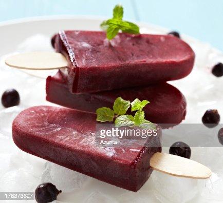 Three dark red ice pops with garnish : Stock Photo