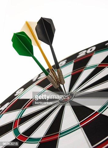 Three darts perfectly on target on a dartboard