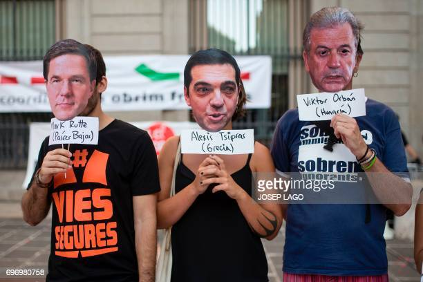 Three demonstrators hold masks with the faces of Dutch Prime Minister Mark Rutte Greek Prime Minister Alexis Tsipras and Hungary's Prime Minister...