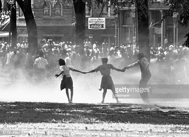 Three demonstrators join hands to build strength against the force of water sprayed by riot police in Birmingham Alabama during a protest of...