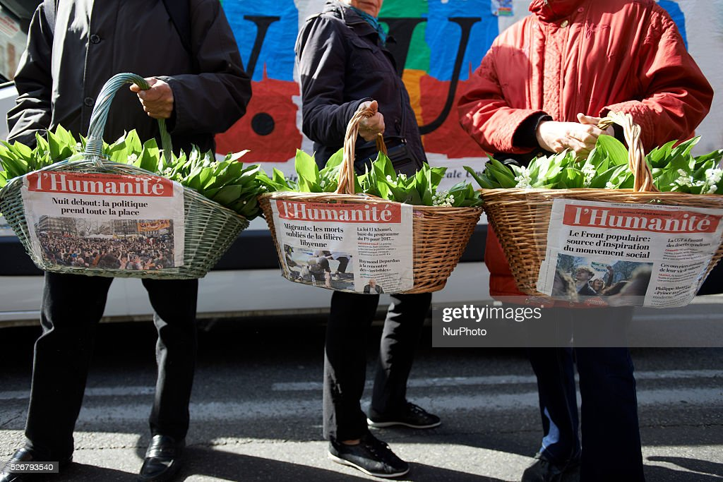 Three demonstrators sell Lily of the valley during the traditionnal march for Labor Day on May 1st with titles of the Humanit�� (founded by socialist leader Jean Jaur��s at the beginning of the XXth century) newspaper glued.Toulouse. France. May 1st 2016.