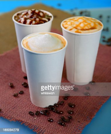 Three different lattes with coffee beans