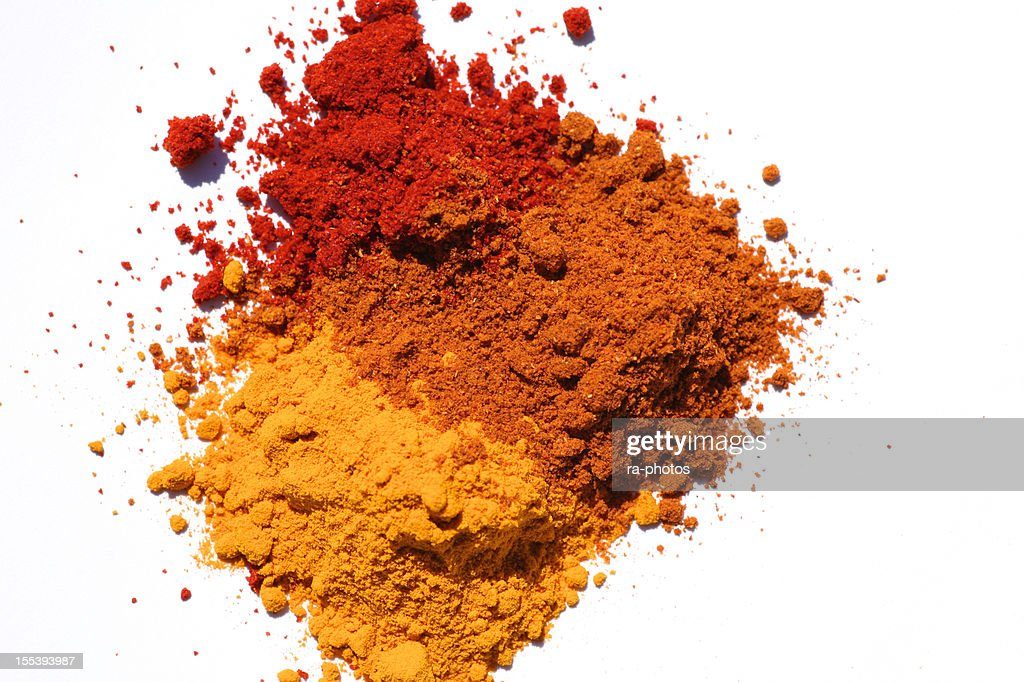 Three different powdered spices in a white background