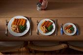 Drei unterschiedlich große Portionen Essen auf Teller