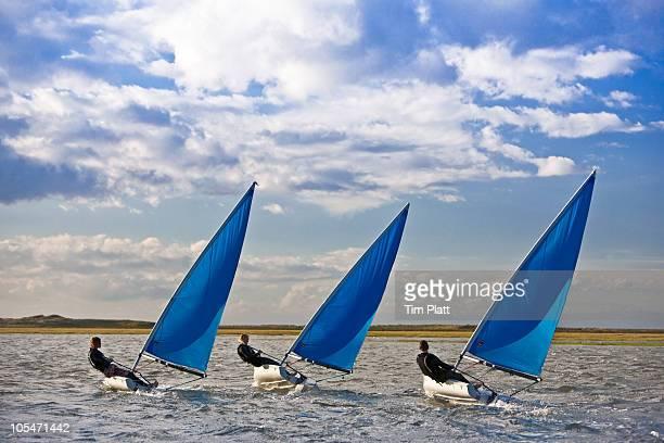 Three dinghy sailors racing together.