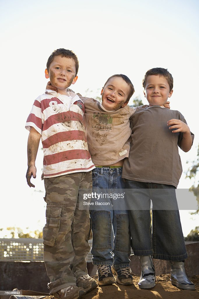 Three dirty boys (6-7, 8-9)  posing outdoors, portrait : Stock Photo