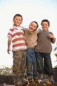 Three dirty boys (6-7, 8-9)  posing outdoors, portrait