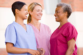 Nurses Standing Outside A Hospital Having A Conversation With Each Other