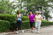 Multiethnic women are exercising in the park by power walking.  They are middle-aged.  They are walking down a gray concrete walkway that is lined with shrubs.  Two are walking almost side by side, wh