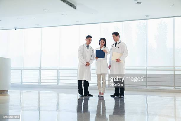 Three doctors standing and looking down at a document in the hospital, full length