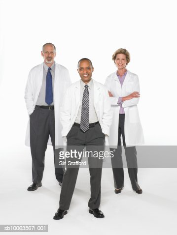 Three doctors standing on white background, portrait : Stock Photo