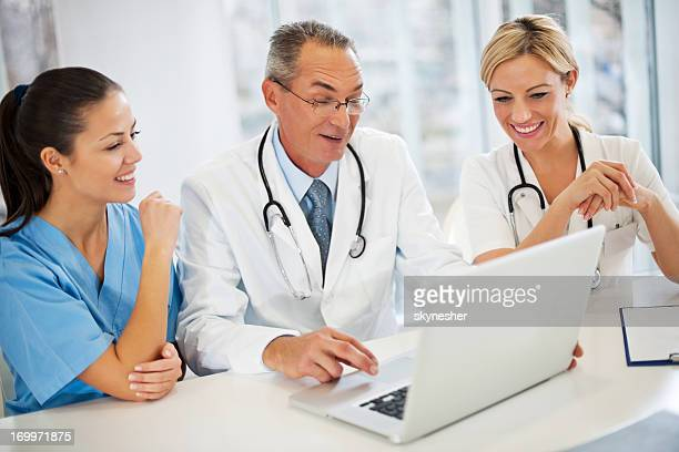 Three doctors working on a laptop.