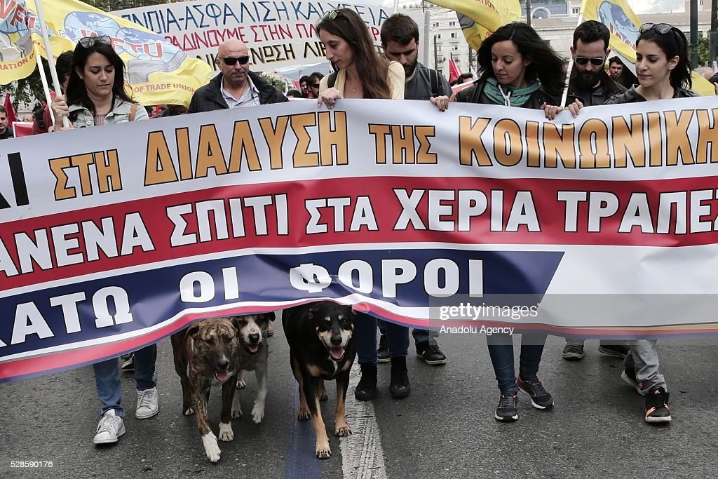 Three dogs are seen under a banner as protestors march during a general strike, against the reform packages including austerity policies in Athens, Greece on May 6, 2016.