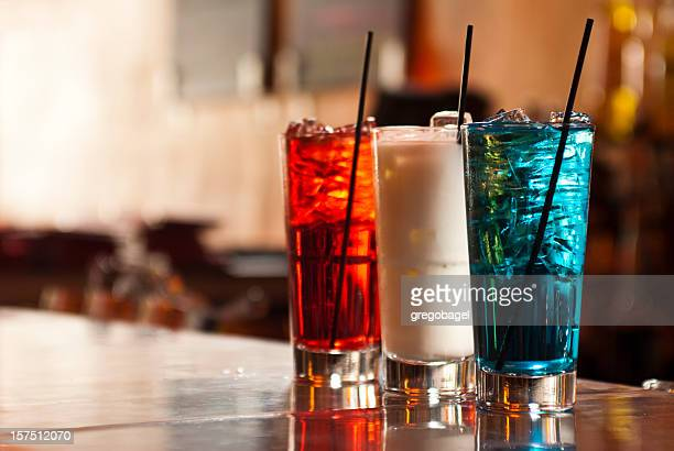 Three drinks sitting on  a bar with American colors