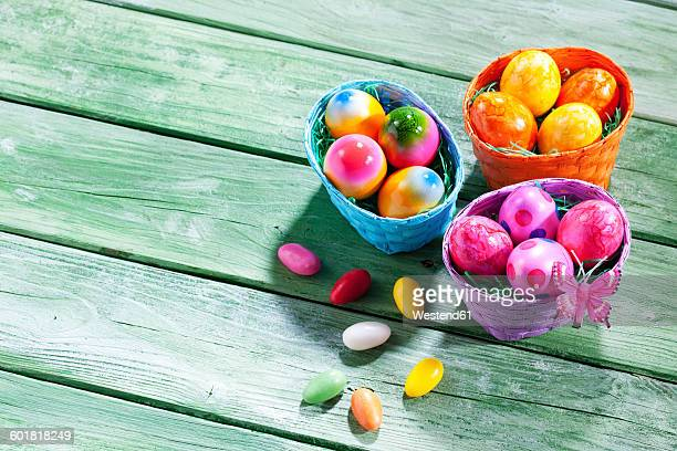 Three Easter nests with coloured Easter eggs on green wood